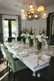 Love the unique modern chandelier with the heavily grained marble dining  table.
