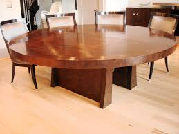 big round brown wooden dining table with two legs also brown wooden chairs with back placed