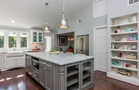 Kitchen with gray island and white cabinets with white marble counters