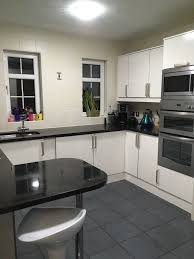 whole white gloss kitchen with black granite worktops
