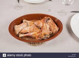 Spanish Roast Leg Of Baby Lamb In Ceramic Tray On Brown Linen Stock