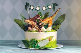 children s holiday white cake decorated with mastic figurines of dinosaurs in the juric period jungle