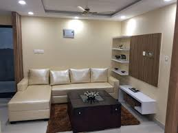 living room with creamy sofa false ceiling and display unit