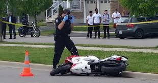 a police officer photographs the scene of a fatal motorcycle accident in milton ont