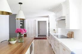 gorgeous kitchen features a pair of white and gold pendants oversized cone shade pendants illuminating a wood top island