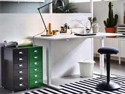 office corner. An Office Setting With Sit/stand Desk, Green And Black Cabinets,  Ergonomic Corner