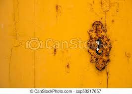 rusty vine keyhole on a yellow door csp50217657