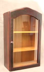 a fabulous little vintage single glass door wall cabinet with two shelves and a wood handle