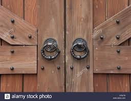 ancient wooden gate with two door knocker rings close-up Stock ...