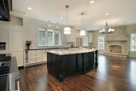 interior white stone fireplace added by black wooden kitchen islands on dark brown wooden floor