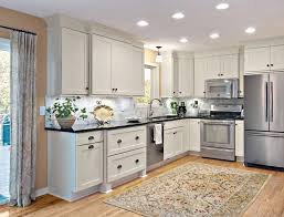 closeup of light rail skirt trim on painted linen shaker cabinets with gray marble backsplash and