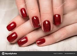 女性の手に明るいお祝いの赤のマニキュア爪をデザインします