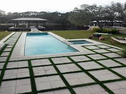 swimming pool concrete pavers artificial grass fake synthetic turf pool house table blue water lounges chairs