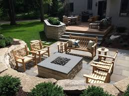 entertaining area with new wood deck raised limestone planter and walls bluestone patio and