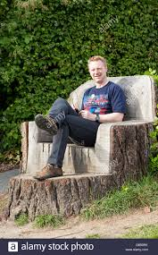 Tree Stump Seats A Man Sits On A Seat Carved From A Tree Stump Stock Photo Royalty