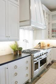 white kitchen range hood with steel straps view full size