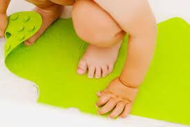 baby crouching on a bath mat