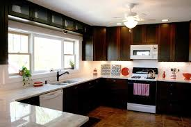 modern classic kitchen design with white appliances and dark brown kitchen cabinets on brown ceramic floor plus white ceiling fan with yellow fitted lamps
