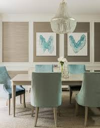 features stacked decorative wall moldings filled with taupe grasscloth lined with turquoise blue inkblot style art over a light taupe sideboard cabinet