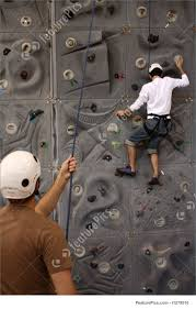 an unidentifiable climber is climbing on an artificial rock wall while another is keeping him