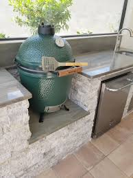 custom outdoor kitchen with built in big green egg grill