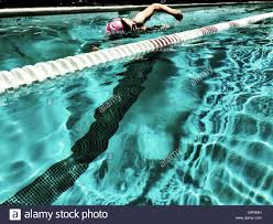 view from adjacent lane young woman swimming freestyle australian crawl in outdoor olympic
