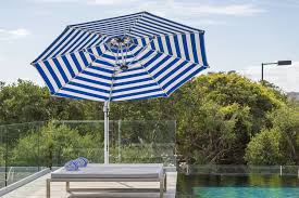 octagonal cantilever umbrella in blue and white stripe poolside