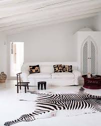 a large zebra print rug and dark stools accentuate a white living room