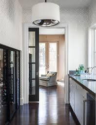 a black pocket door with glass panels opens to a long butler s pantry featuring walls clad in white and gray trellis wallpaper fitted with a built in wine