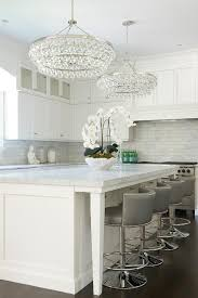 illuminating a center island with legs topped with carrera marble lined with gray leather barrel back counter stools with silver nailhead trim