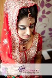 a uk asian bride on her wedding day she is wearing traditional red coloured wedding clothes and traditional bridal makeup