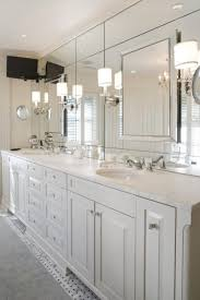 modern bathroom wall sconces with large frameless mirror above double sink bathroom vanity under recessed lights