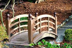 this is an example of a small garden bridge in wood rather than bridging the expanse over water feature structure crosses natural ditch japanese bridges