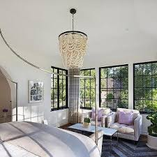 small bedroom sitting area with cream tufted chairs and lilac pillows view full size a pottery barn amelia indoor outdoor wood bead chandelier