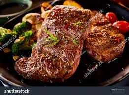 cooked meat. Wonderful Meat Close Up On Marinated And Cooked Meat Garnished With Rosemary Broccoli  Tomatoes Onion With Cooked Meat N
