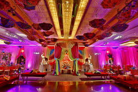 a colorful indian wedding reception with elephants and umbrellas