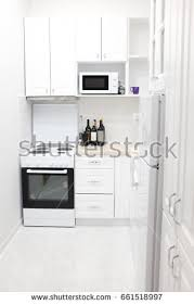kitchen furniture white. House Kitchen Vertical Perspective With White Wooden Cupboards, Oven Stoves, Bottles Of Wine Furniture