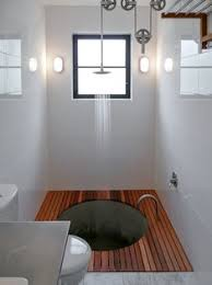 a pulley system adjusts the shower height above a sunken concrete bathtub bespoke shower system by lance work