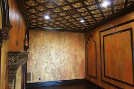 grand middle eastern sitting room with gold leafed ceiling textured wall finish faux wood grained columns and fireplace and gold detailed moldings