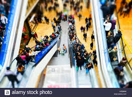 people on escalators. escalator escalators up and down people shopping mall centre travelling using a crowded moving walkway birmingham on p