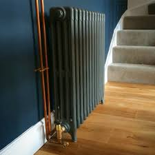 Refurbished cast iron radiator with brass valves. Copper pipes left exposed  and coated. Wall