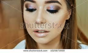 makeup artist paints s lips model in gentle pink color