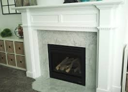 white wooden fireplace mantel with tile around and black metal