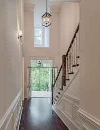 two story foyer with carriage lantern and dark stained wood floors vintage south development