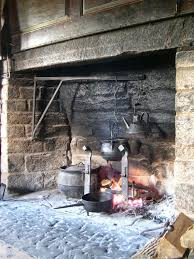 swinging iron arms protruding from the surrounding stone or brick held massive pots enabling the cook the luxury of moving the pots closer to or further