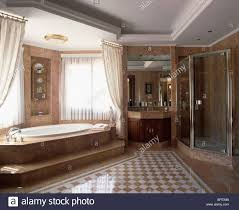Modern Marble Bathroom Steps Up To Oval Bath With Cream Drapes In Modern Marble Bathroom