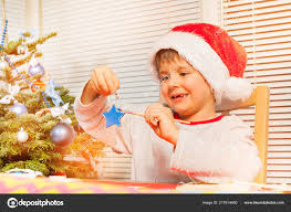 portrait of preschool boy in santa s costume holding wooden star and decorating it with blue paint photo by