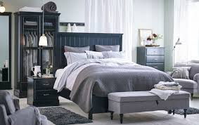 A large bedroom with a big black bed standing in the middle of the room,