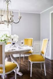 stunning dining room features gray walls paired with wainscoting framing french chandelier over round gray dining home decor