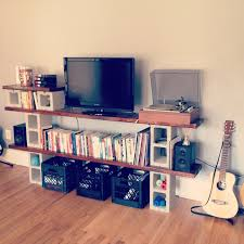 concrete block and wooden a and book shelf with basket storage placed on brown laminated wooden floor with cinder block shelves with candles and